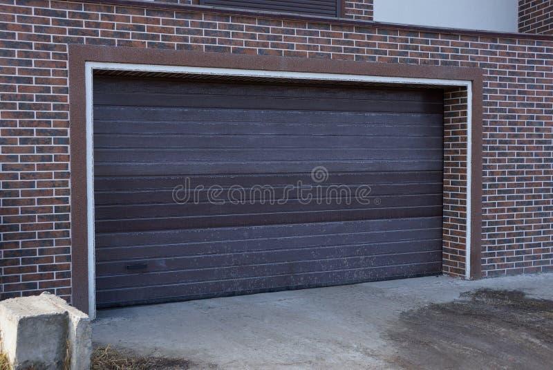 Puerta marrón cerrada en la pared de ladrillo de un garaje al aire libre fotos de archivo