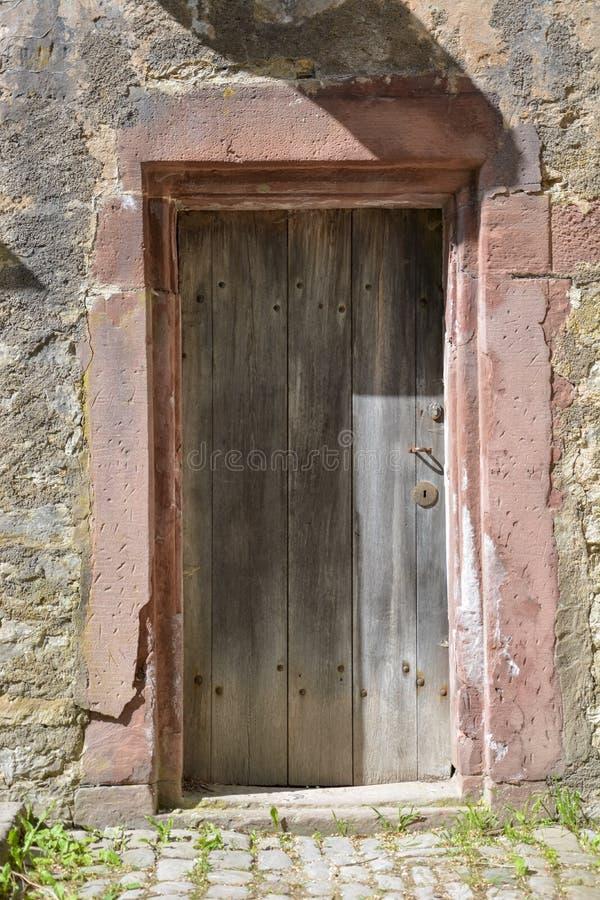 Puerta medieval de madera vieja en una pared de piedra en un día soleado foto de archivo