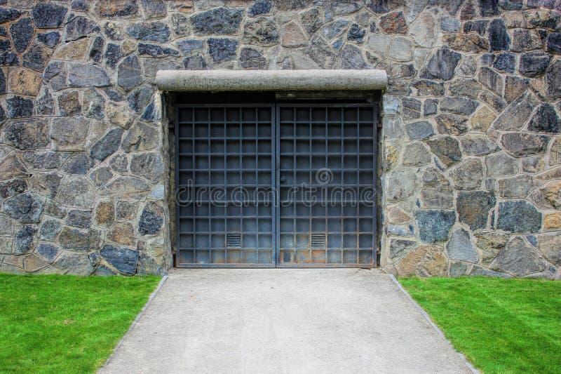 Puerta o puerta de acero en una pared de piedra vieja, garaje, césped verde del metal fotos de archivo