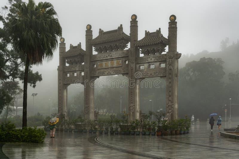 Puerta ornamental debajo de las fuertes lluvias en Po Lin Buddhist Monastery, Hong Kong China imagenes de archivo