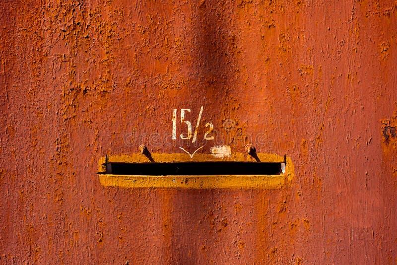Puerta pintada roja vieja del metal del primer con las fracciones dos del número quince y el agujero del correo Textura horizonta imágenes de archivo libres de regalías