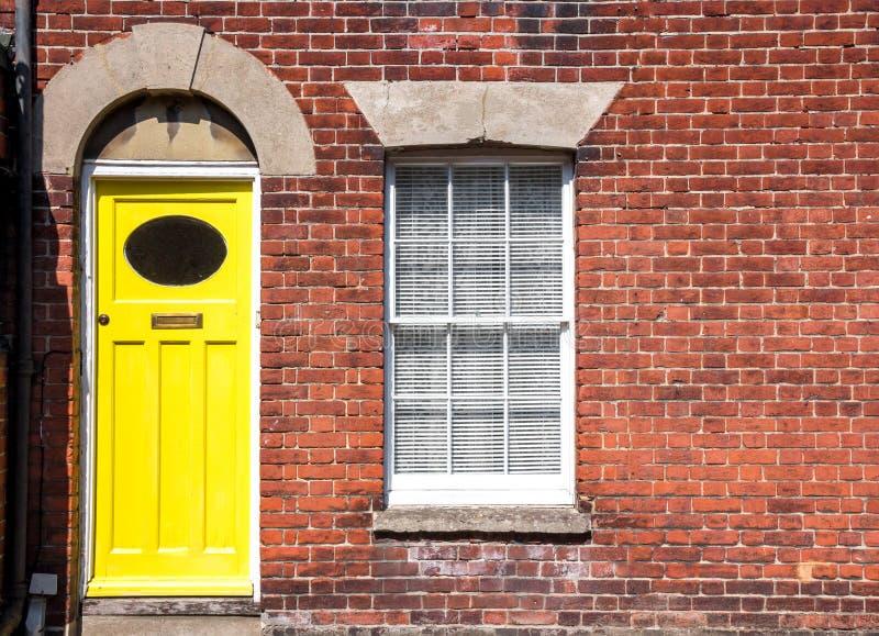 Puerta principal amarilla de una casa colgante inglesa tradicional vieja fotos de archivo libres de regalías