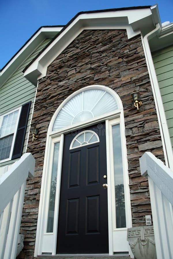 Puerta principal de un hogar con una fachada de piedra. fotografía de archivo libre de regalías
