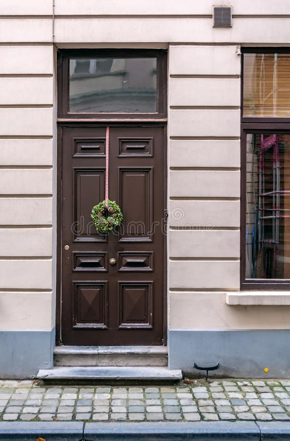 Puerta principal marrón del vintage adornada con la guirnalda de la Navidad fotos de archivo