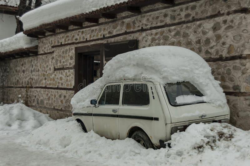 Puerta principal y coche de la cubierta de la nieve acumulada por la ventisca en invierno en Bansko imagen de archivo