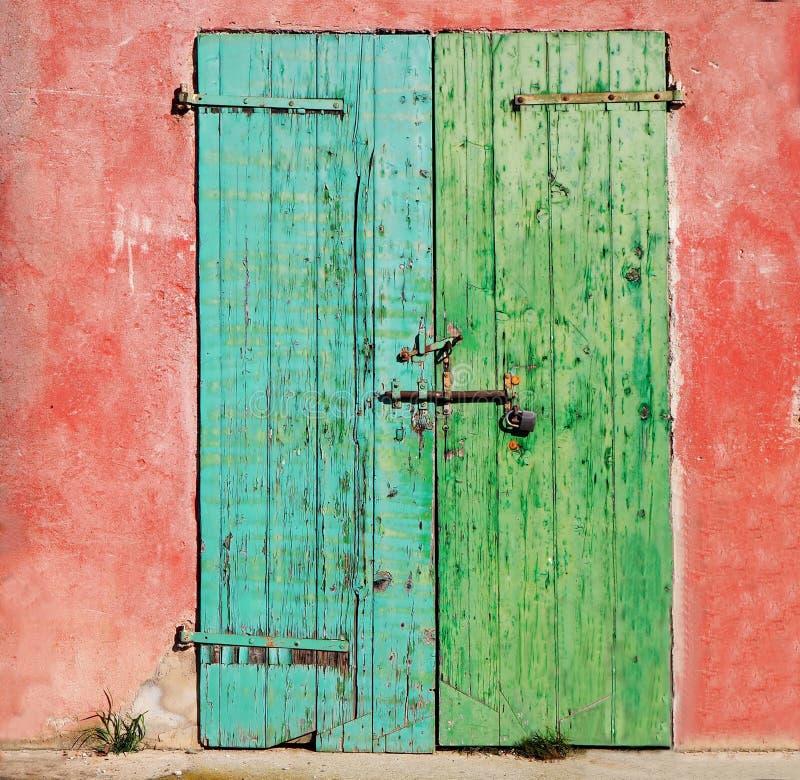 Puerta resistida de madera vieja pintada en un lado de turquesa y en el otro verde, con la cerradura y el candado oxidados La par fotos de archivo
