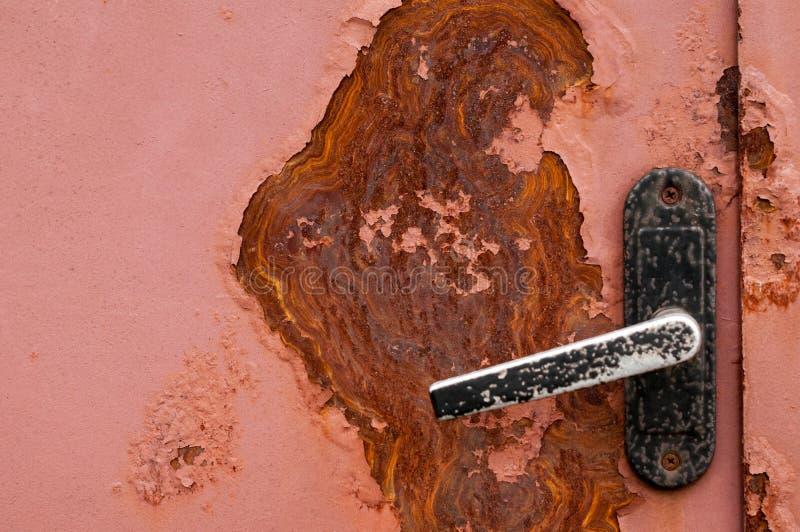 Puerta roja cerrada del metal con el punto grande del moho y el bot?n de puerta negro fotografía de archivo libre de regalías