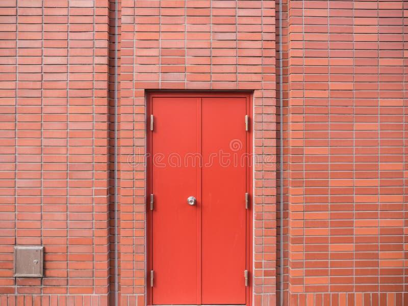 Puerta roja de acero en la pared de ladrillo roja foto de archivo