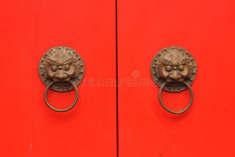 Puerta roja del chino tradicional con el botón en un templo viejo fotografía de archivo