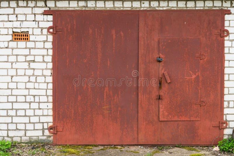 Puerta roja envejecida del garage del metal foto de archivo