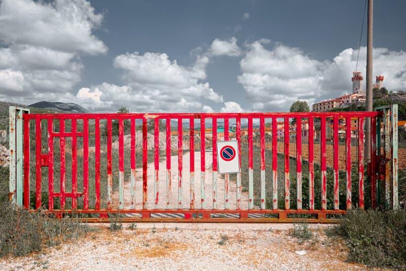 Puerta roja que bloquea el acceso a un camino de tierra en el campo toscano, concepto del bloque imagen de archivo libre de regalías