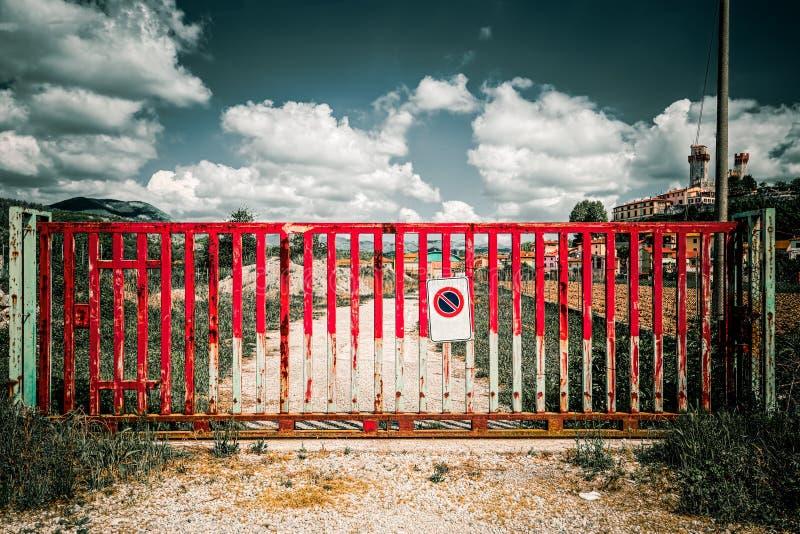 Puerta roja que bloquea el acceso a un camino de tierra en el campo toscano, concepto del bloque dramático imagenes de archivo