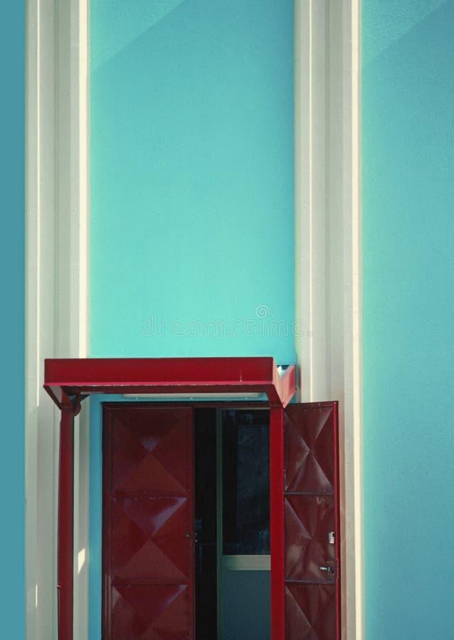 Puerta roja y edificio azul imágenes de archivo libres de regalías