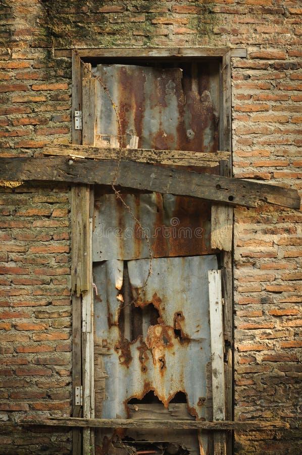 Puerta rota vieja en una pared de ladrillo imagen de for Como barnizar una puerta vieja