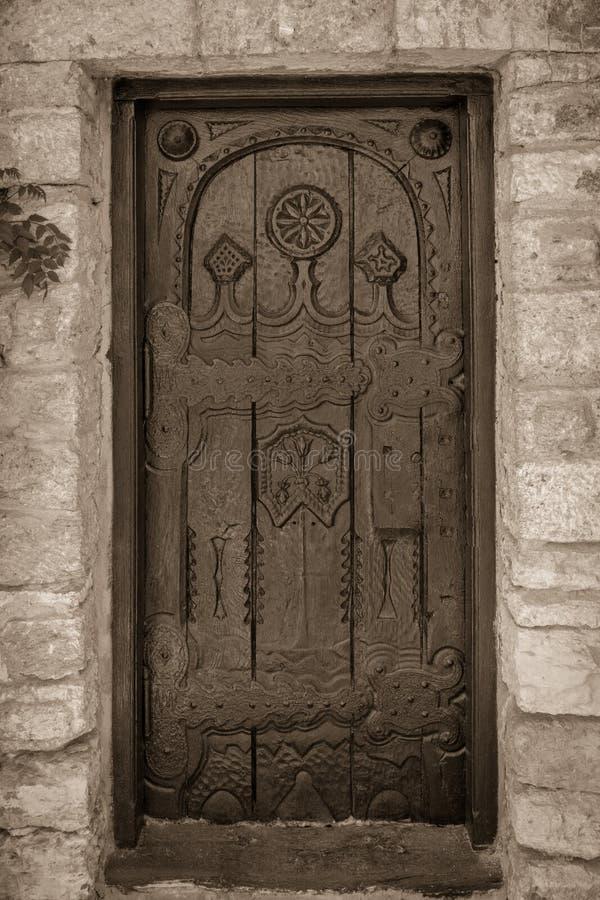 Puerta tallada vieja monocromática en bulding de una piedra e hindges grandes fotos de archivo libres de regalías