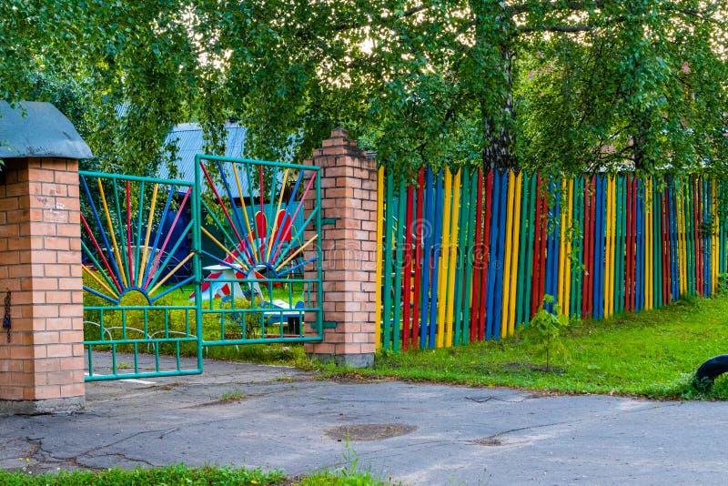Puerta torcida al patio Cerca y puerta multicoloras en la guardería rural fotografía de archivo