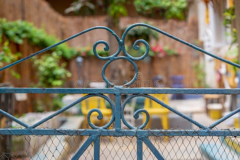 Puerta verde artística del hierro labrado del vintage con la pintura de la peladura y moho que revela el jardín borroso fotos de archivo