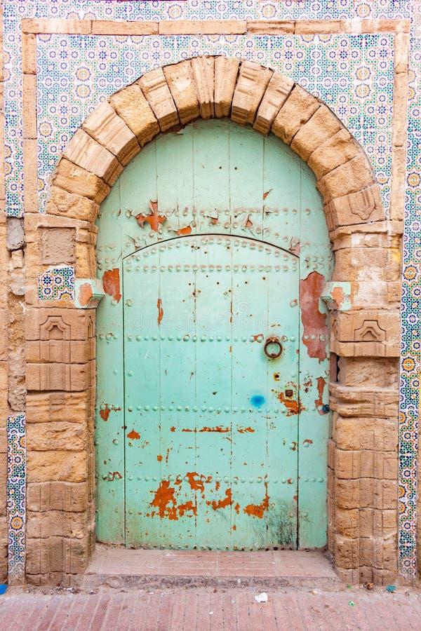 Puerta verde de lujo en Essaouira Marruecos rodeado por las tejas coloridas fotografía de archivo