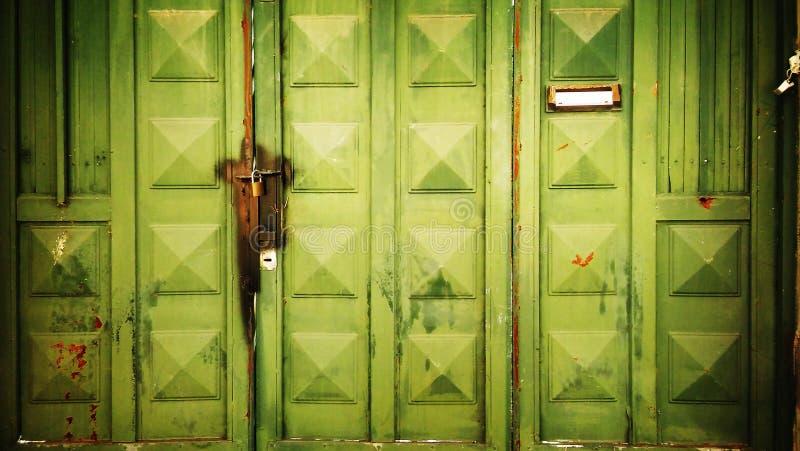 Puerta verde hecha de la hoja de metal oxidada asegurada con los candados imágenes de archivo libres de regalías