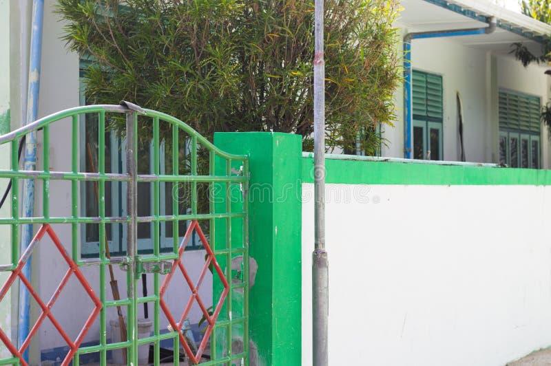 Puerta verde y roja de una casa maldiva imagenes de archivo