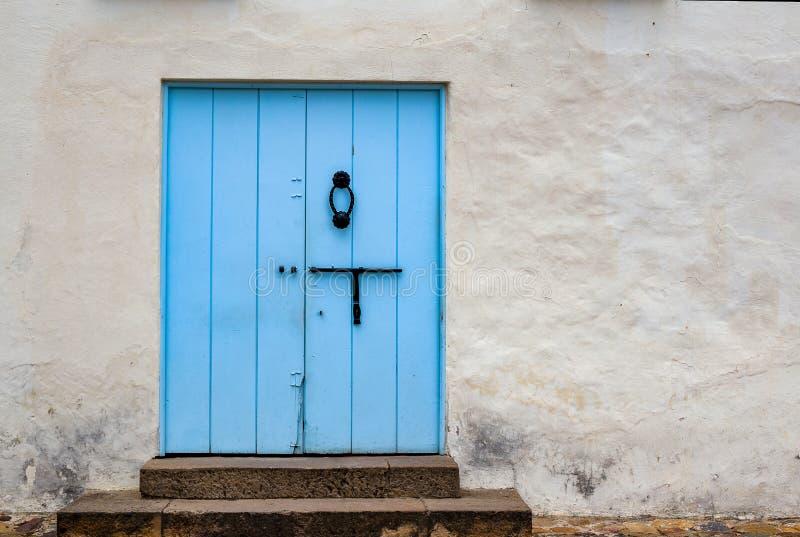 Puerta vieja azul claro en una calle fotos de archivo