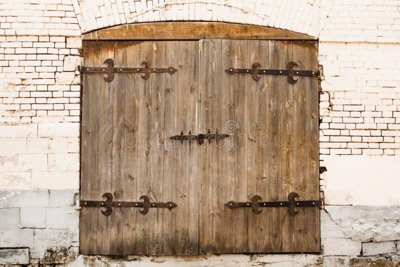 Puerta vieja con la cerradura en la pared de ladrillo foto de archivo libre de regalías