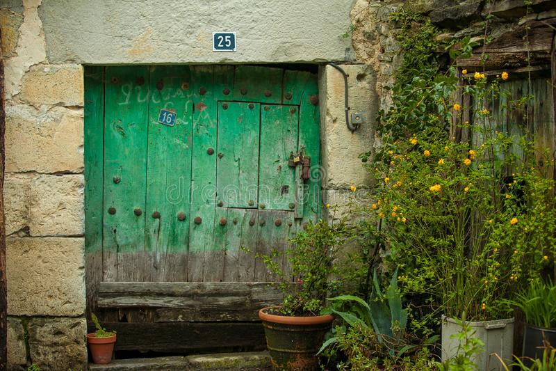 Puerta vieja cuadrada hecha de la madera de piedra y verde imágenes de archivo libres de regalías