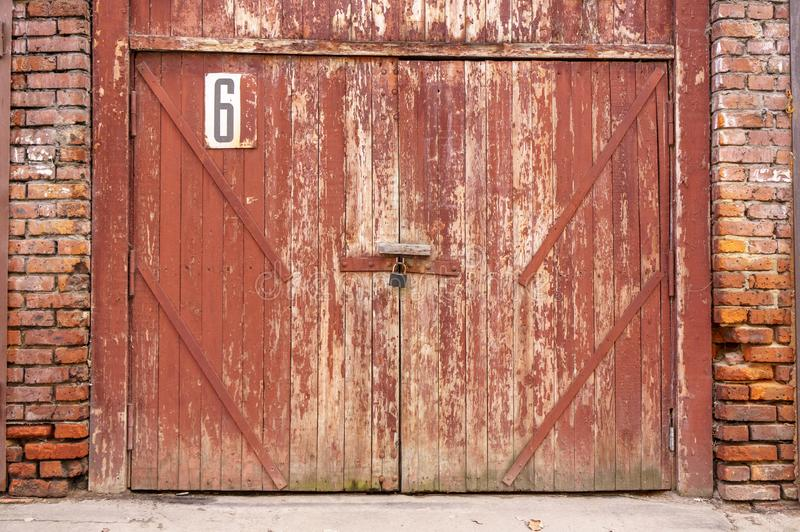 Puerta vieja del garaje en un muro de cemento blanco Puertas hechas de la madera pintada con la pintura verde agrietada fotos de archivo libres de regalías
