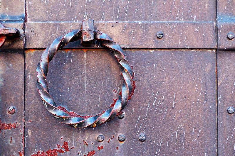 Puerta vieja del metal del grunge con los remaches y el tirador de puerta oxidado torcido bajo la forma de anillo foto de archivo libre de regalías