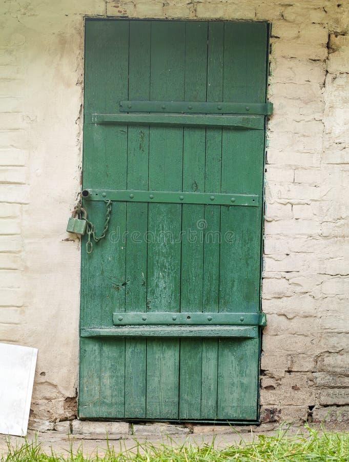 Puerta vieja del metal y de madera con una cerradura oxidada foto de archivo
