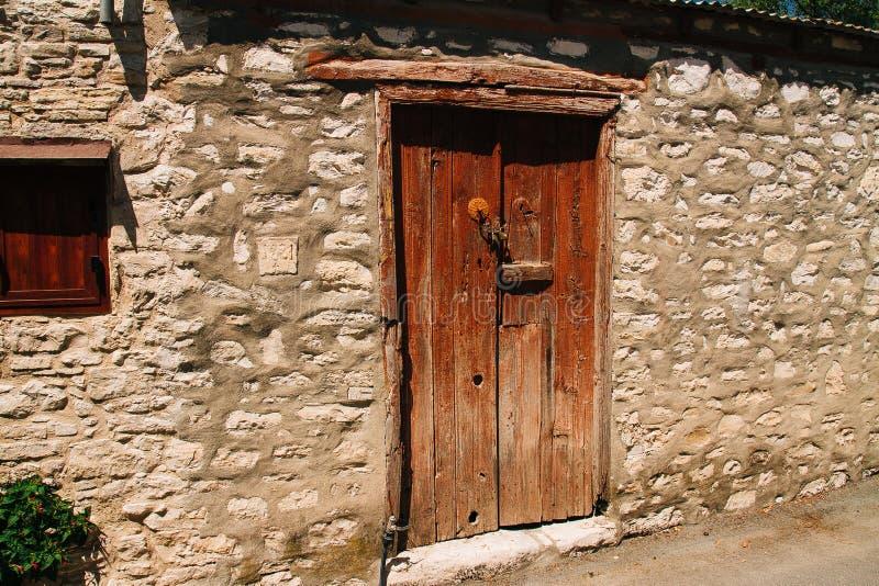 Puerta vieja del vintage en una pared de piedra en el pueblo de Laneia Limas imagenes de archivo