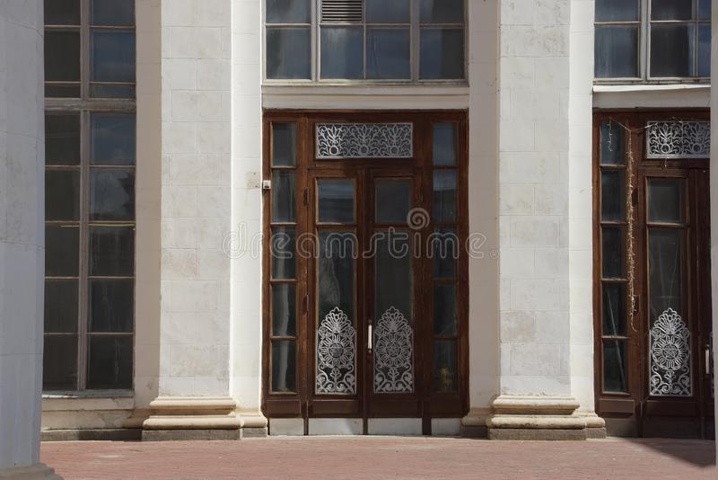 puerta vieja marrón de la madera y del vidrio en un muro de cemento gris con las columnas fotos de archivo libres de regalías