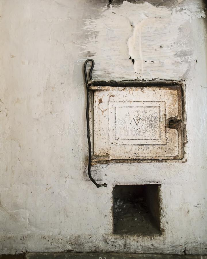 Puerta y póker del arrabio para el carbón en una estufa rusa tradicional, vieja foto de archivo libre de regalías