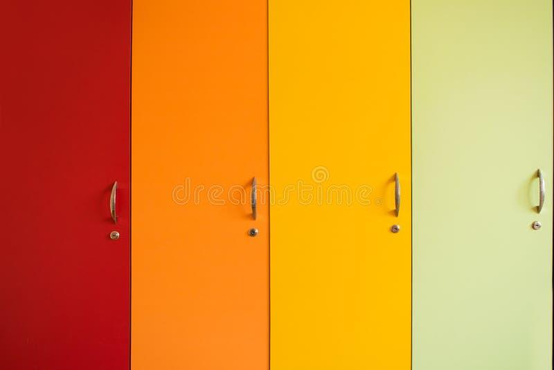 Puertas brillantes coloridas de gabinetes con las manijas Furnitur del arco iris foto de archivo