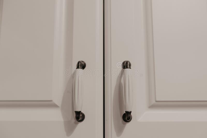 Puertas con las manijas blancas del armario en la cocina imagen de archivo libre de regalías