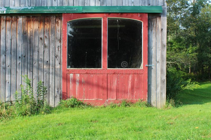 Puertas de granero rojas con las ventanas grandes en pista verde en un edificio de madera resistido fotos de archivo