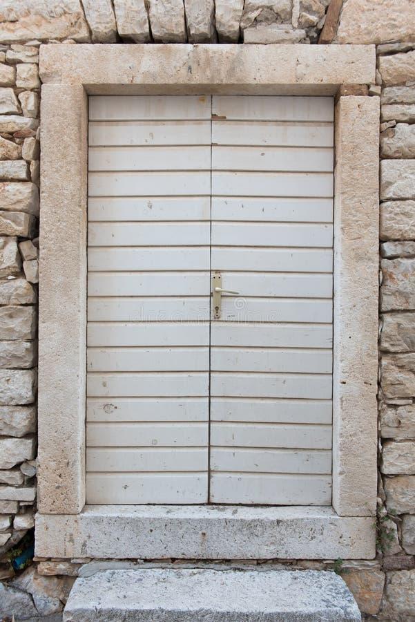 Puertas de madera blancas cerradas viejas con el marco de piedra en una casa de piedra fotos de archivo libres de regalías