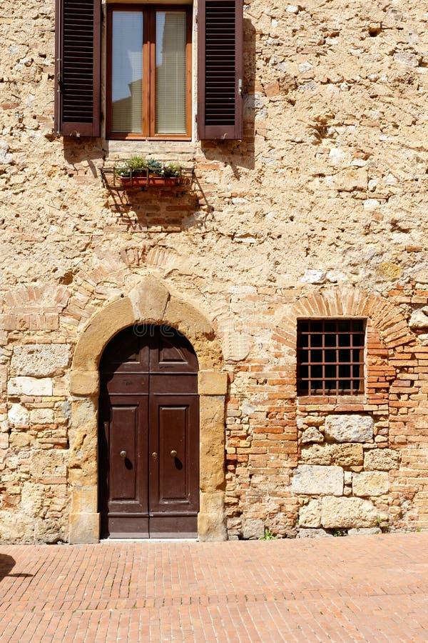 Puertas de madera de Brown en una pared de piedra vieja imagen de archivo