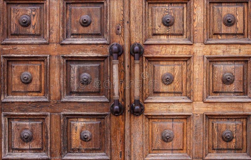 Puertas de madera lamentables muy viejas con las manijas grandes en el museo foto de archivo
