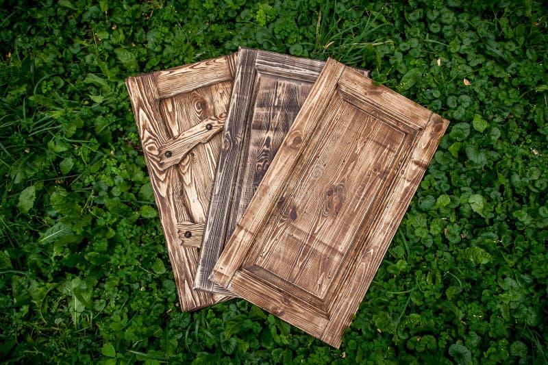 Puertas de madera que mienten en hierba en parque foto de archivo