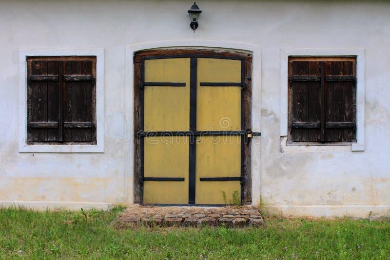 Puertas de madera renovadas con las persianas de ventanas de madera cerradas foto de archivo libre de regalías