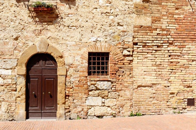 Puertas en pared de ladrillo antigua en campo toscano italiano fotos de archivo