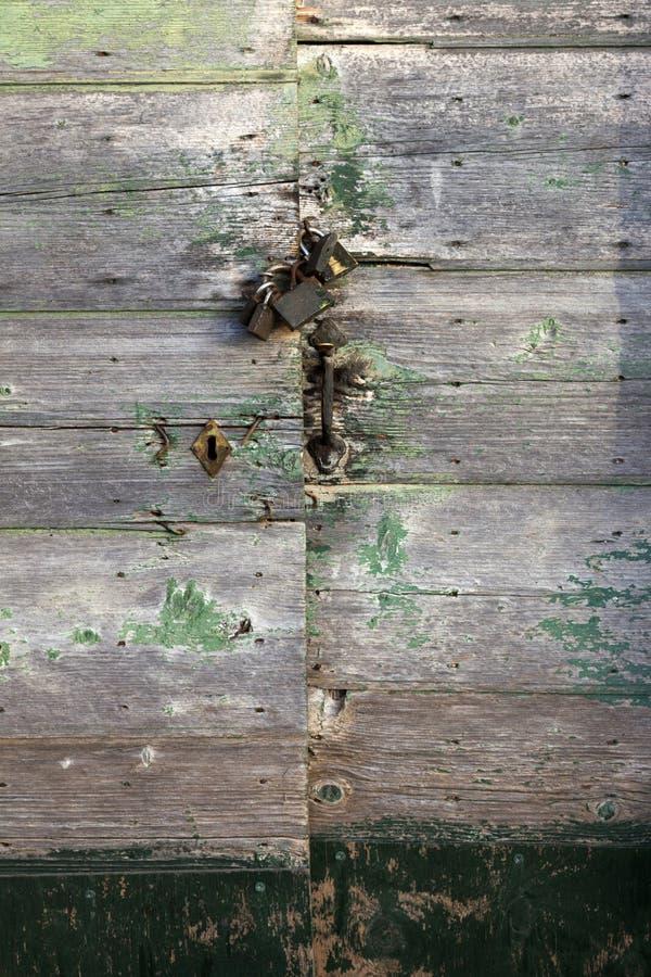 Puertas muy viejas en griego el edificio del griego clásico con los candados y el verde imagenes de archivo