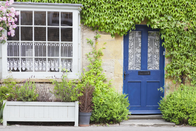 Puertas principales azules en la casa vieja rodeada por las plantas verdes fotografía de archivo