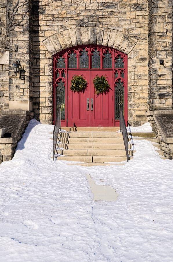 Puertas rojas de la iglesia con las guirnaldas fotografía de archivo libre de regalías