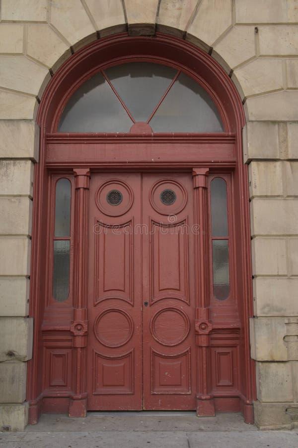 Puertas rojas históricas y arcada de piedra foto de archivo libre de regalías