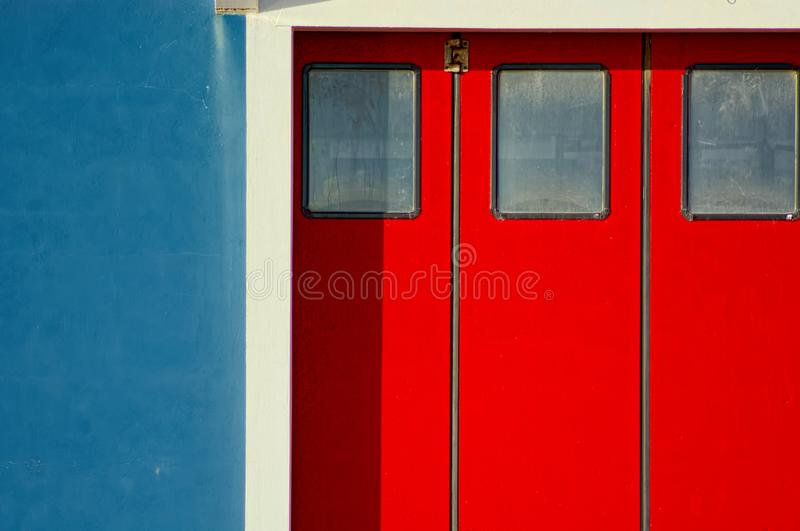 Puertas rojas vivas, pared azul, ajuste blanco Color abstracto imágenes de archivo libres de regalías