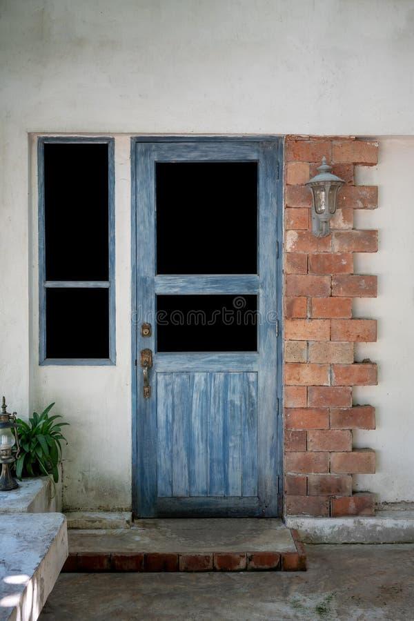 Puertas y ventana de madera antiguas con la pared de ladrillo y el cordero rojos imagenes de archivo