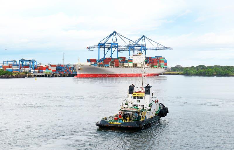Puerto格查尔,危地马拉 运转的猛拉小船在有集装箱船的港口在背景中 免版税库存图片