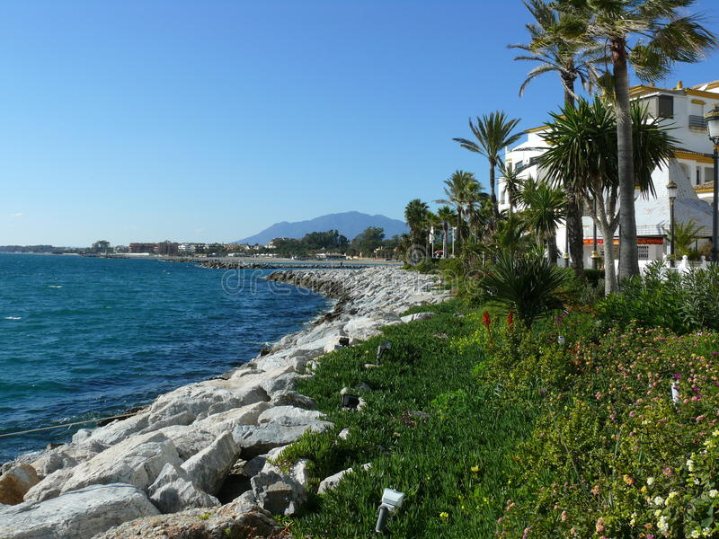 Puerto Banus view of the coastline. Scenic winter view at day time in Puerto Banus, Spain. In the photo are exterior buildings, the sea, stones, trees, plants stock photos